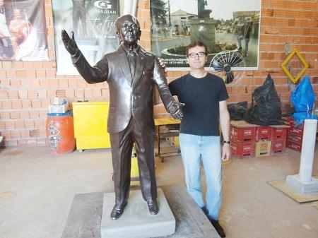Cláudio ao lado da escultura do saudoso professor Paulo Ribeiro.